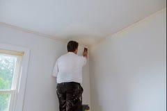 Επισκευή δωματίων, χέρι που στρώνει με άμμο τον τοίχο με ένα στρώνοντας με άμμο σφουγγάρι Στοκ Εικόνες
