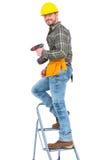 Επισκευαστής με τη μηχανή τρυπανιών που αναρριχείται στη σκάλα Στοκ εικόνα με δικαίωμα ελεύθερης χρήσης