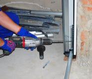 Επισκευαστής που εγκαθιστά την πόρτα γκαράζ στοκ φωτογραφία
