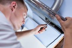 Επισκευαστής που επιδιορθώνει έναν εξολκέα κουζινών στοκ φωτογραφία