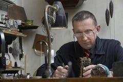 Επισκευαστής που εργάζεται σε ένα παλαιό ρολόι στοκ εικόνες