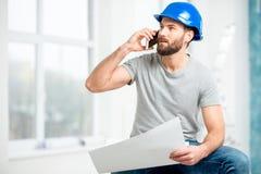Επισκευαστής που μιλά με το τηλέφωνο στο διαμέρισμα Στοκ Φωτογραφία