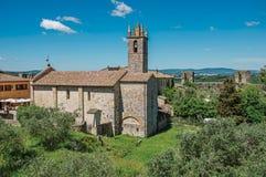 Επισκόπηση του πύργου εκκλησιών και κουδουνιών με τα δέντρα γύρω στο χωριουδάκι Monteriggioni στοκ φωτογραφίες