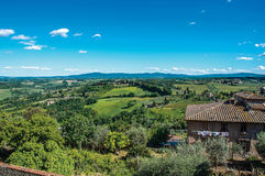 Επισκόπηση του σπιτιού με τους πράσινους Tuscan λόφους στο υπόβαθρο και το μπλε ουρανό στο SAN Gimignano στοκ φωτογραφίες