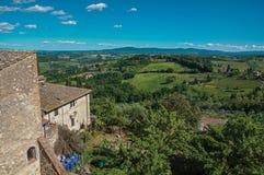 Επισκόπηση του σπιτιού με τους πράσινους Tuscan λόφους στο υπόβαθρο και το μπλε ουρανό στο SAN Gimignano Στοκ φωτογραφίες με δικαίωμα ελεύθερης χρήσης