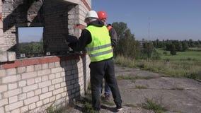 Επιστάτης και εργαζόμενος κατασκευής που μιλούν ο ένας με τον άλλον φιλμ μικρού μήκους