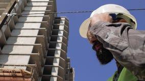 Επιστάτης κατασκευής σε ένα κράνος κοντά στο εργοτάξιο οικοδομής μιας πολυκατοικίας 4 Κ φιλμ μικρού μήκους