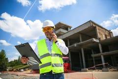 Επιστάτης στην εργασία ομοιόμορφη expertising η δομή που στέκεται με το φάκελλο στο εργοτάξιο οικοδομής στοκ φωτογραφία