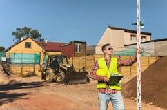 Επιστάτης στο υπόβαθρο κατασκευής με μια περιοχή αποκομμάτων στα χέρια του Στοκ Εικόνες