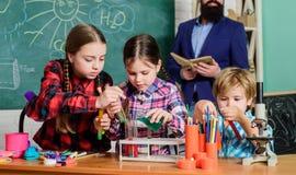 Επιστήμη και εκπαίδευση εργαστήριο χημείας o ευτυχής δάσκαλος παιδιών παιδιά που κάνουν τα πειράματα επιστήμης στοκ εικόνα