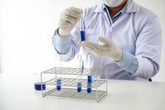 Επιστήμονας ή ιατρικός στο σωλήνα δοκιμής εκμετάλλευσης παλτών εργαστηρίων με το αντιδραστήριο, στοκ εικόνες