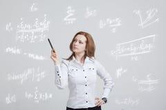 Επιστήμονας ή σπουδαστής γυναικών με τη μάνδρα που λειτουργεί με τον τύπο διάφορων γυμνασίου μαθηματικών και επιστήμης Στοκ Εικόνες