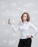 Επιστήμονας ή σπουδαστής γυναικών με τη μάνδρα που λειτουργεί με τον τύπο διάφορων γυμνασίου μαθηματικών και επιστήμης Στοκ Φωτογραφία