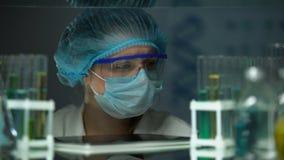 Επιστήμονας που αναλύει τους σωλήνες με τα υγρά και που ελέγχει τα αποτελέσματα στην ετικέττα, καινοτομίες απόθεμα βίντεο
