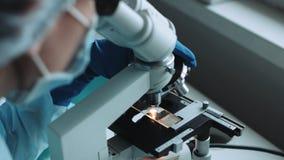 Επιστήμονας που εργάζεται στο εργαστήριο με το μικροσκόπιο απόθεμα βίντεο
