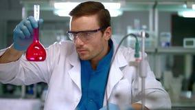 Επιστήμονας που ελέγχει το σωλήνα δοκιμής με το ρόδινο υγρό Εργαστηριακός ερευνητής φιλμ μικρού μήκους