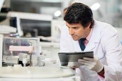 Επιστήμονας που παρατηρεί το πείραμα στοκ εικόνες
