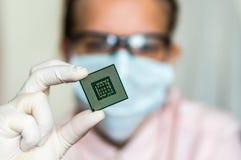 Επιστήμονας που παρουσιάζει μικροτσίπ υπολογιστών πριν από το ηλεκτρόνιο επισκευών στοκ εικόνες