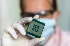 Επιστήμονας που παρουσιάζει μικροτσίπ υπολογιστών πριν από το ηλεκτρόνιο επισκευών στοκ φωτογραφία