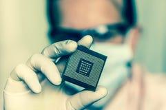 Επιστήμονας που παρουσιάζει μικροτσίπ υπολογιστών πριν από το ηλεκτρόνιο επισκευών στοκ εικόνες με δικαίωμα ελεύθερης χρήσης