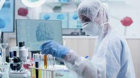 Επιστήμονας στην άσπρη φόρμα και τα προστατευτικά γυαλιά που λειτουργούν με τους σωλήνες δειγμάτων απόθεμα βίντεο