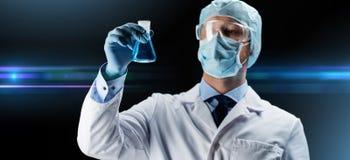 Επιστήμονας στη φιάλη εκμετάλλευσης μασκών με τη χημική ουσία στοκ εικόνες με δικαίωμα ελεύθερης χρήσης