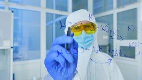 Επιστήμονας στο προστατευτικό κοστούμι που γράφει τους χημικούς τύπους στο γυαλί απόθεμα βίντεο