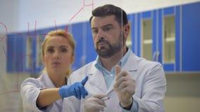 Επιστήμονες που συσκέπτονται ο ένας με τον άλλον γράφοντας κάτω τις χημικές εξισώσεις φιλμ μικρού μήκους