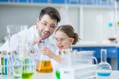 Επιστήμονες σπουδαστών δασκάλων και κοριτσιών ατόμων στα προστατευτικά γυαλιά που κάνουν το πείραμα Στοκ φωτογραφία με δικαίωμα ελεύθερης χρήσης