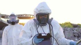 Επιστήμονες στα προστατευτικές κοστούμια και τις μάσκες και ένα δοσίμετρο, ακτινοβολία μέτρου περιπάτων στο υπόβαθρο των καταστρο απόθεμα βίντεο