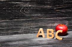 Επιστολές αλφάβητου και κόκκινο μήλο σε ένα μαύρο υπόβαθρο Το concep Στοκ φωτογραφίες με δικαίωμα ελεύθερης χρήσης