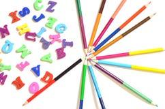 Επιστολές χρώματος του αγγλικού αλφάβητου Δίπλα σε τους είναι χρωματισμένα μολύβια Τοπ όψη Παιδιά διδασκαλίας Στοκ Φωτογραφία