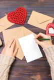 Επιστολή αγάπης γραψίματος γυναικών ή ρομαντικό ποίημα για την ημέρα βαλεντίνων, τοπ άποψη των θηλυκών χεριών Έννοια ημέρας βαλεν στοκ φωτογραφία