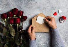 Επιστολή αγάπης φακέλων εκμετάλλευσης χεριών ατόμων ημέρας βαλεντίνων με τη ευχετήρια κάρτα Στοκ Φωτογραφία