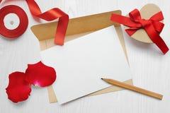 Επιστολή ευχετήριων καρτών ημέρας βαλεντίνων προτύπων στο φάκελο με το κιβώτιο δώρων του Κραφτ, flatlay σε ένα άσπρο ξύλινο υπόβα Στοκ φωτογραφίες με δικαίωμα ελεύθερης χρήσης