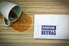 Επιστολή με σε γερμανικό Rundfunkbeitrag στην αγγλική ραδιο θέση και ένα υποκείμενο σε ντάμπινγκ φλυτζάνι καφέ από τον τρόμο στοκ εικόνες με δικαίωμα ελεύθερης χρήσης