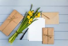 Επιστολή, φάκελος, δώρα και daffodils στο γκρίζο υπόβαθρο Η ρομαντική έννοια διακοπών, τοπ άποψη, επίπεδη βάζει στοκ φωτογραφίες