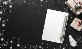 Επιστολή Χριστουγέννων, κατάλογος, συγχαρητήρια σε ένα υπόβαθρο blaack, δώρα στο κιβώτιο και τον κώνο πεύκων Χριστούγεννα και άλλ Στοκ Φωτογραφίες