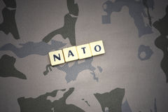 Επιστολές με το ΝΑΤΟ κειμένων στο χακί υπόβαθρο τεθωρακισμένων επιθέσεων πράσινο m4a1 στρατιωτικό τουφέκι s σημαιών έννοιας σωμάτ Στοκ εικόνες με δικαίωμα ελεύθερης χρήσης