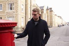 Επιστολή ταχυδρόμησης ατόμων στο κόκκινο βρετανικό ταχυδρομικό κουτί Στοκ εικόνες με δικαίωμα ελεύθερης χρήσης