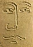 Επισύρετε την προσοχή το πρόσωπο στην άμμο Στοκ Φωτογραφία