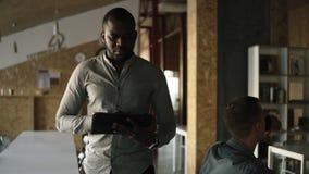 Επιταχυνόμενο μήκος σε πόδηα Το νέο συγκεντρωμένο αφροαμερικανός επιχειρησιακό άτομο περπατά με μια ταμπλέτα στο χέρι και τη δακτ απόθεμα βίντεο
