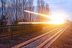 Επιταχυνόμενο τραίνο με τις δραματικές ελαφριές ραβδώσεις Στοκ Φωτογραφία