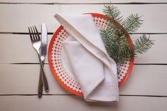 Επιτραπέζια θέση Χριστουγέννων που θέτει με τα πιάτα γευμάτων, πετσέτα, μαχαιροπήρουνα, έλατο Στοκ εικόνες με δικαίωμα ελεύθερης χρήσης