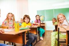 Επιτραπέζιες σειρές με τα αγόρια και τα κορίτσια που φαίνονται ευθέα Στοκ Φωτογραφία