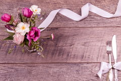 Επιτραπέζιες τοποθετήσεις θέσεων με το δίκρανο και το μαχαίρι, που δένονται με μια άσπρη κορδέλλα σατέν, και λουλούδια σε μια εκλ Στοκ Εικόνα