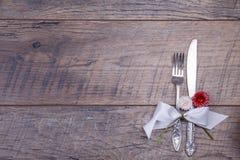 Επιτραπέζιες τοποθετήσεις θέσεων με το δίκρανο και το μαχαίρι, που δένονται με μια άσπρη κορδέλλα σατέν, και λουλούδια σε μια εκλ Στοκ εικόνα με δικαίωμα ελεύθερης χρήσης