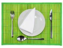 Επιτραπέζιο εξυπηρετώ-μαχαίρι, κουτάλι, δίκρανο στο πράσινο σκηνικό. Στοκ Εικόνες