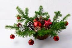 Επιτραπέζιο κεντρικό τεμάχιο Χριστουγέννων με τις κόκκινες διακοσμήσεις και το αγροτικό άχυρο Στοκ Εικόνα