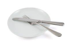 Επιτραπέζιο μαχαίρι, δίκρανο και κεραμικό πιάτο που απομονώνονται Στοκ Εικόνες